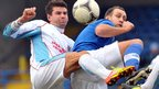Mark McCullagh of Ballymena United competes for the ball with Glenavon striker Guy Bates