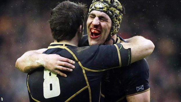 Bloodied Scotland captain Kelly Brown hugs number eight Johnnie Beattie after their bruising win at home to Ireland