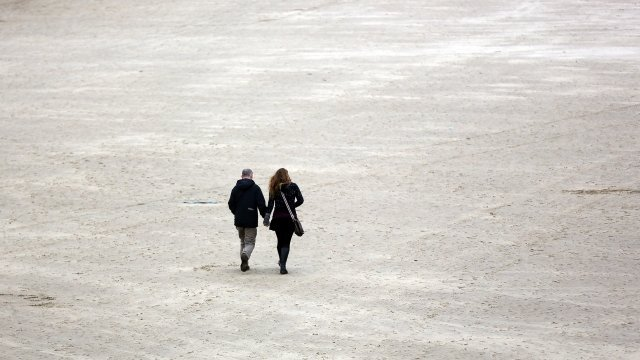 A couple walk on the beach