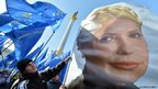 A man holds a flag bearing a picture of jailed former Prime minister Yulia Tymoshenko