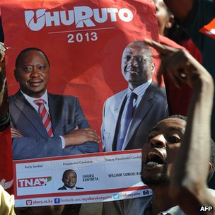 Supporters of The National Alliance hold a poster showing Uhuru Kenyatta (L) and his running mate William Ruto