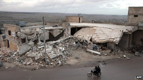 Syrians ride a motorcycle past the remains of a building allegedly destroyed by an explosive device dropped from a Syrian warplane in the town of Kfar Nubul, Idlib province (11 February 2013)