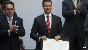 Mexico's president, Enrique Pena Nieto, shows signed education reform document