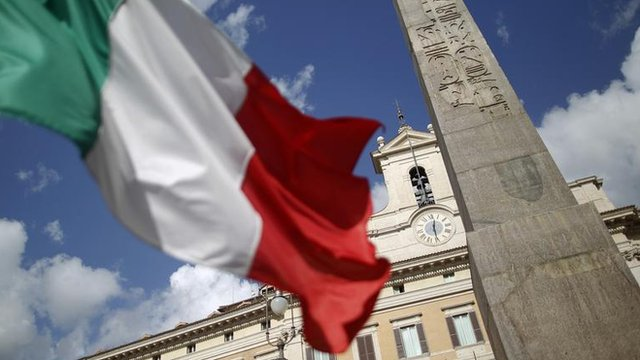 An Italian flag in front of the Montecitorio palace in Rome