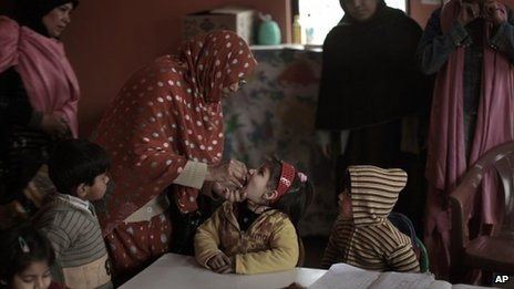 Pakistani health workers gives a polio vaccine to child, at a kindergarten in Islamabad, Pakistan on 30 January