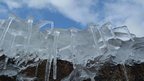 Icicles like spider legs hanging down over a rock. Blue sky behind.