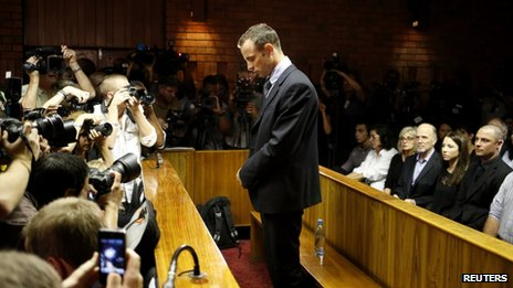 Oscar Pistorius stands at the dock before the start of proceedings at a Pretoria magistrates court on 22 February 2013