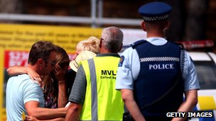 People grieve outside the Muriwai Surf Lifesaving Club after a swimmer died in a fatal shark attack at Muriwai Beach on 27 February 2013 in Auckland, New Zealand