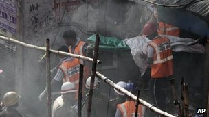 "Rescue workers carry a victim""s body wrapped in plastic bag after a fire at an illegal market in Kolkata"