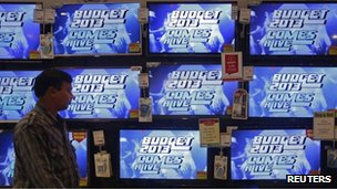 "A man walks past television screens showing an advertisement for a program on India""s annual budget at an electronics shop in Mumbai in this February 22, 2013"