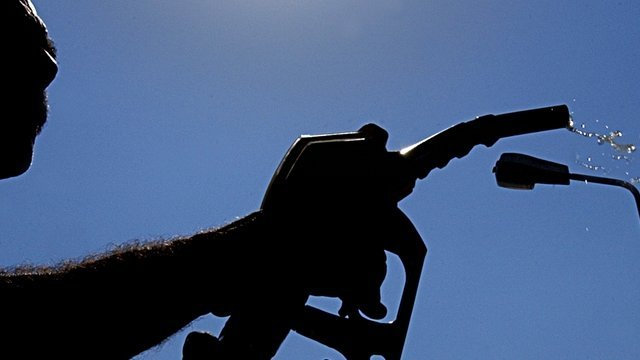 A man in silhouette fills up at a petrol station