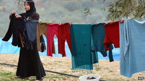 A displaced Syrian refugee her washed clothes at the refugee camp of Qah along the Turkish border in the village of Atme in the northwestern province of Idlib, on January 31 2012.