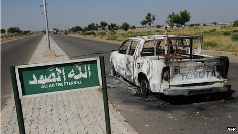 A burnt police patrol pick-up truck remains abandoned on the side of a deserted road in Damaturu in Nigeria  on 7 November 2011 after having been struck by a bomb