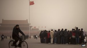 A police officer in plain clothes rides a bicycle past tourists pose for a group photo on Tiananmen Square on a hazy day in Beijing, China, 28 February 2013