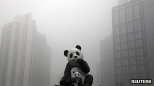 Panda statues are seen in front of buildings on a hazy day in Beijing, 28 February 2013