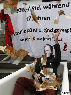 A protester wearing a mask with Vasella portrait throws fake banknotes during a demonstration before Swiss drug maker Novartis annual shareholders general meeting in Basel