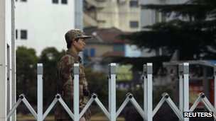 """A Chinese People's Liberation Army soldier stands guard in front of """"Unit 61398"""", a secretive Chinese military unit, in the outskirts of Shanghai, February 19, 2013"""