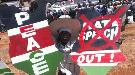 A person holding up signs calling for peace and ending hate speech at a peace concert in Nairobi, Kenya, 28 February 2013