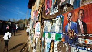 People walk past campaign posters in Nairobi's Kibera slum on 27 February  2013
