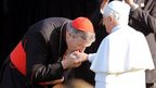 A cardinal kisses Pope Benedict XVI's hand, file pic