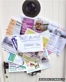 "Dozens of leaflets pinned to a front door under a note saying ""no more thank you""."