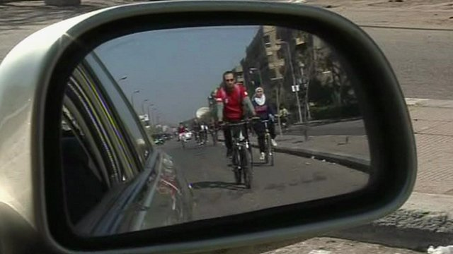 A cyclist seen in the side mirror of a car