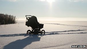 Baby sleeping in pram, in snowy field