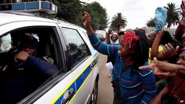 Residents shout at a police vehicle as they protest the death of taxi driver Mido Macia