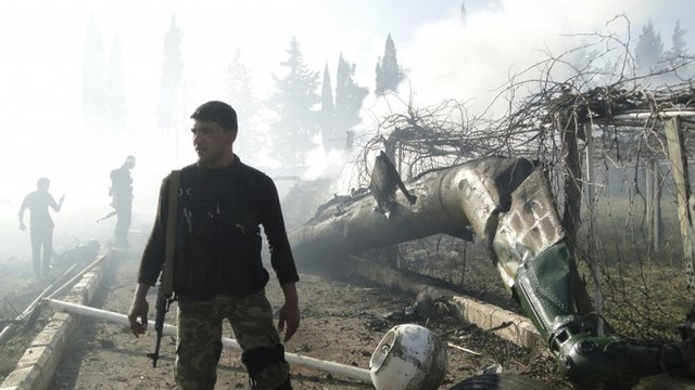 Members of Free Syrian Army inspect wreckage of a helicopter belonging to forces loyal to President Bashar al-Assad
