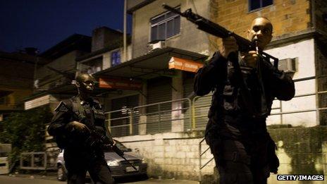 Brazilian police officers with assault rifles patrolling the Caju shantytown in Rio de Janeiro
