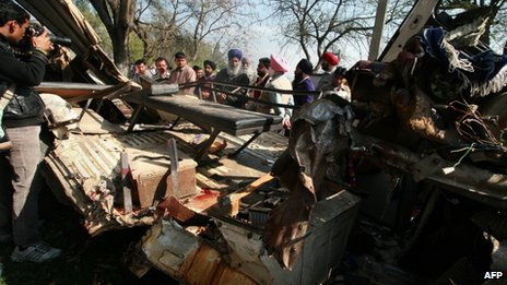 Indian villagers look at the damaged school bus in which at least eleven school children died when the school bus collided with a truck in Jaheer village, in Jalandhar district on March 4, 2013.