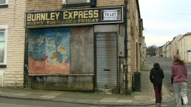 Children walking past a boarded up shop in Burnley