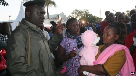 A woman holding her child is assisted by a police officer in Kisumu, Kenya -Monday 4 March 2013