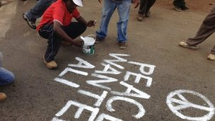 "Solomon Muyundo painting ""Peace Wanted Alive"" all over Kibera"