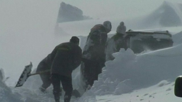 Workers dig out a car buried in snow