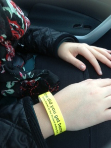 A yellow safety wrist band on a minibus passenger