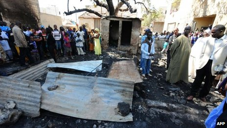 People look at the scene of the fire at a Koranic school in Dakar, Senegal (4 March 2013)