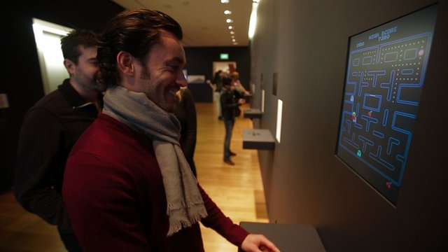 Man watches PacMan at the MoMA