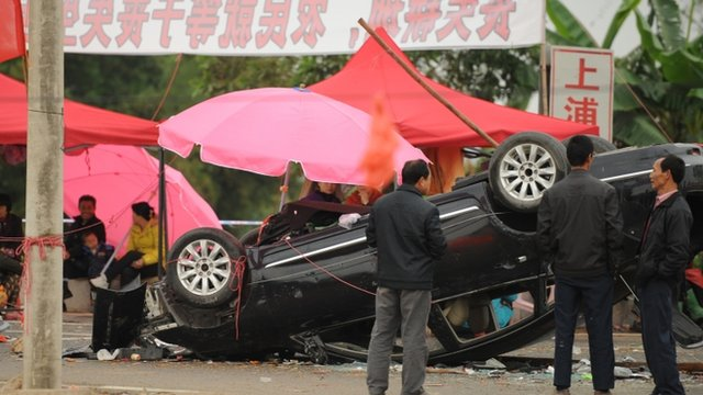 Residents look at smashed and overturned cars after civil unrest in the village of Shangpu in China's southern Guangdong province