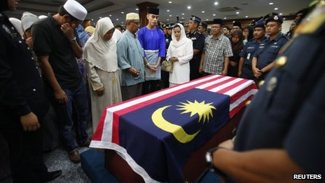 Relatives pray next to the coffin of a Malaysian policeman killed in Sabah state (4 March 2013)