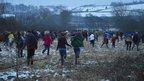 Spectators chase the ball across fields