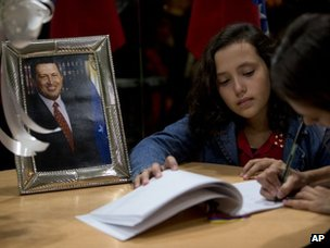 Women sign a book of condolence at the Venezuelan embassy in Buenos Aires
