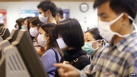 Unemployed people wearing masks look for jobs at a job centre in Hong Kong to protect against a killer outbreak of pneumonia 15 April 2003.