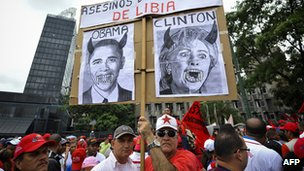 Man holds a protest sign with Hillary Clinton and Barack Obama made to look like demons