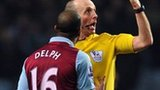 Fabian Delph is booked for deliberate handball by referee Mike Dean
