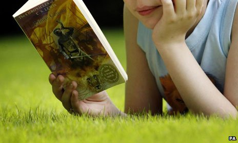 Child reading Narnia book on grass