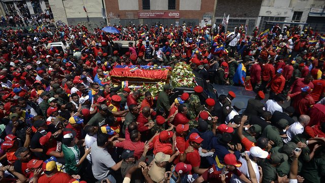 The hearse carrying President Chavez&#039;s coffin passes through packed streets