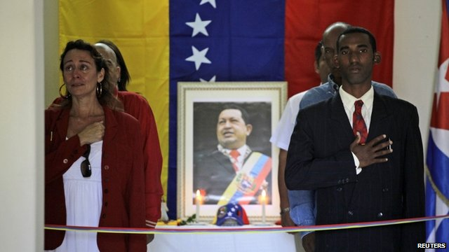 People mourn beside a portrait of the late President Hugo Chavez during a vigil in Venezuela's embassy in Havana