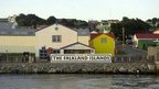 """Shot of houses with a """"Welcome to the Falkland Islands"""" sign in front"""