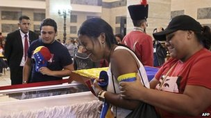 A woman weeps beside the coffin of Hugo Chavez